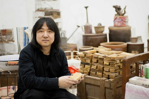 Chinese artist Song Dong poses with old bars of soap at his exhibition at the Barbican Gallery in London Song Dong Waste Not which ends June 12, 2012 Photographer Jane Hobson