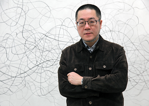 Artist Wang Huangsheng in front of his largest love letter in the show, photo by Chris Phillips